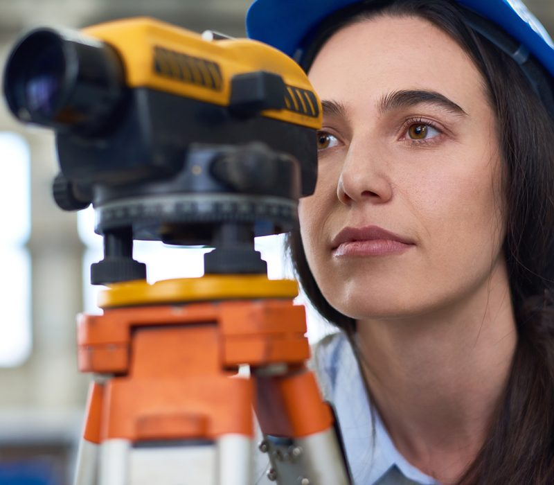 Portrait of female geodesist wearing hardhat looking into optical level mounted on tripod at construction site